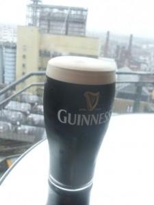 Bierglas Guinness mit Bauerei im Hintergrund